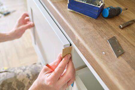 Photo pour Closeup process of assembling kitchen furniture, hands of male worker. Working hands of male carpenter assembling furniture - image libre de droit