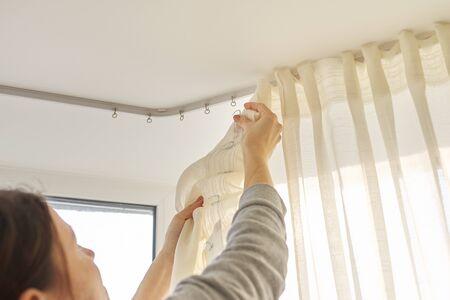 Photo pour Close up of woman hands hanging curtain with metal hooks on ceiling ledge. - image libre de droit