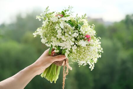 Photo pour Close-up bouquet of fresh flowers rose and lily of the valley in woman hand. Springtime, holidays, wedding, beauty - image libre de droit