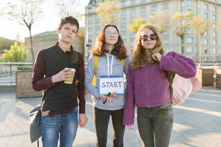 Photo pour Group teenagers boy and two girls, with a notepad with handwritten word start. Teenagers looking forward, city background, golden hour - image libre de droit