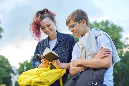 Photo pour Outdoor portrait of two talking teenagers, students boy and girl with notepad, back to school - image libre de droit