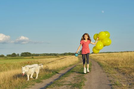 Foto de Dynamic outdoor portrait of running girl with white dog and yellow balloons on country road, beautiful landscape with blue sky and yellow grass in meadow - Imagen libre de derechos