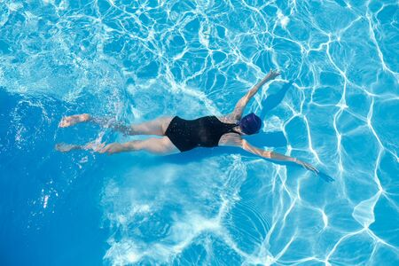 Photo pour Young woman swimming underwater in an outdoor pool, top view of back of girl, active healthy lifestyle of youth - image libre de droit
