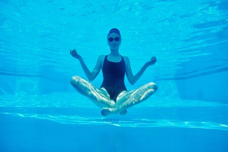Photo pour Young athletic woman sitting in lotus pose underwater in swimming pool. - image libre de droit