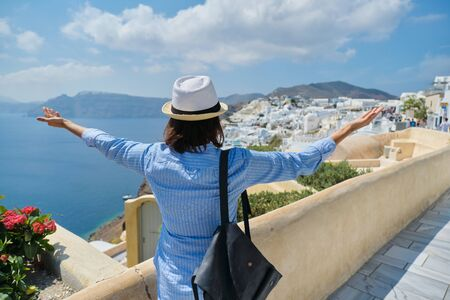 Photo for Happy woman tourist with arms raised up, emotion of freedom success happiness. Rear view of female with hat backpack, landscape of Greek island Santorini, Oia - Royalty Free Image