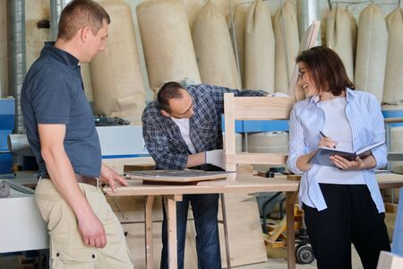 Photo pour People working in carpentry workshop, woman and men workers making sample of wooden chair using design drawing - image libre de droit