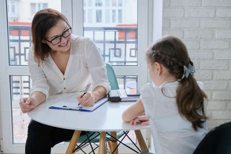 Photo pour Communication session of school psychologist and girl 9, 10 years. Child tells psychotherapist his experiences, mental health of children - image libre de droit
