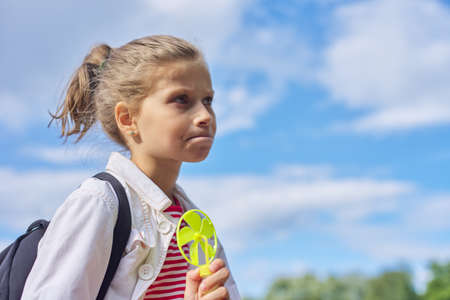 Photo for Girl child blonde 9, 10 years old in profile, head closeup, sky in clouds background, copy space - Royalty Free Image