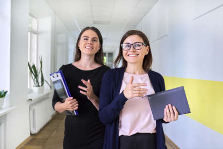 Two colleagues of businesswoman, teacher walking and talking on corridor of office, school. Positive smiling young and middle aged females, business education professions office workers concept