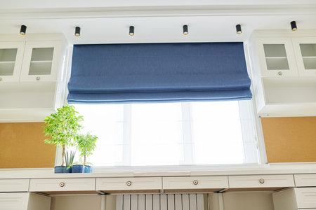 Foto de Roman blind in the interior detail close-up. Curtain blue blackout fabric, sheers white linen, fashionable modern window decoration design at home - Imagen libre de derechos
