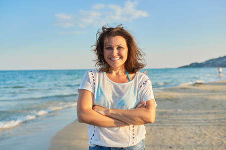 Photo for Portrait of happy smiling confident middle aged woman on beach - Royalty Free Image