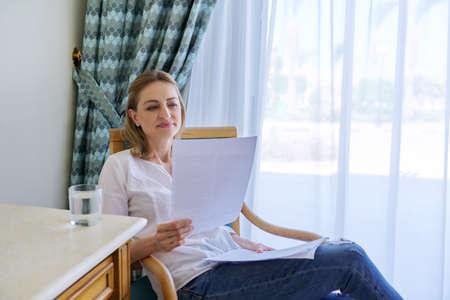 Photo pour Smiling contented middle aged woman reading paper letter - image libre de droit