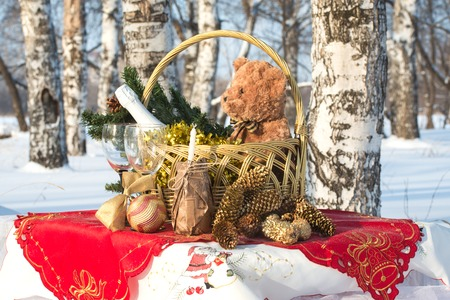 New Year's gift in a basket with decorations on the table in a forest