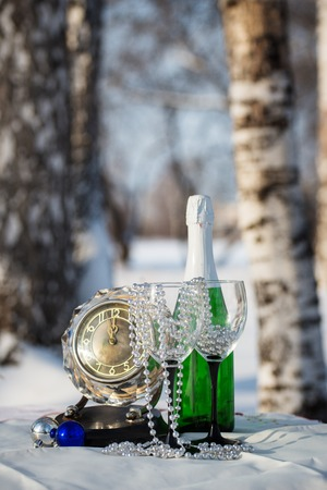 Champagne, glasses, watch  in the winter birchwood