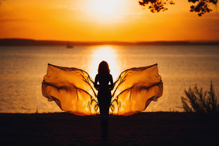 silhouette at sunset on the sea fluttering fabric in the form of a butterfly