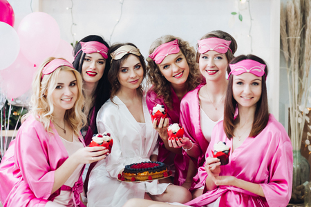 Foto de Pretty girls in pink robes and sleep masks with desserts at bridal showers. - Imagen libre de derechos