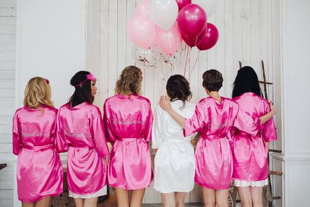 Foto de Bridesmaids in pink silk robes with the word bridesmaid on bac - Imagen libre de derechos