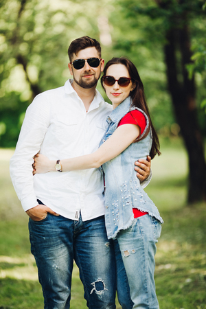 Photo pour Portrait of young happy couple in love, smiling and embracing in garden. - image libre de droit
