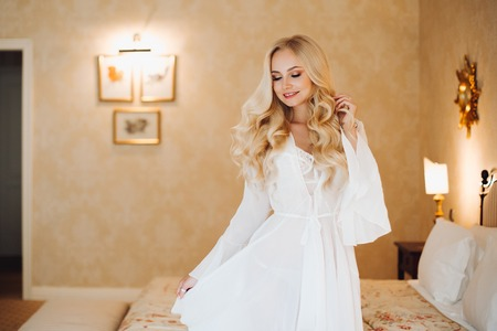 Foto de Sexy bride wearing in white lace lingerie at luxury bedroom interior. - Imagen libre de derechos