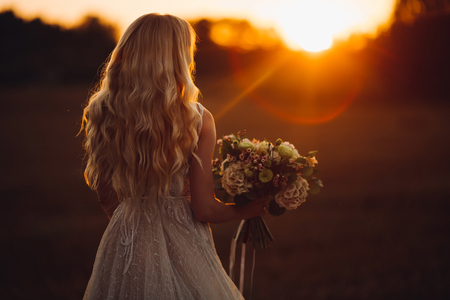 Foto de Unrecognazible blondy bride looking away and holding wedding boquet at sunset. - Imagen libre de derechos