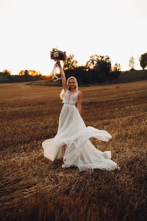 Foto de Blonde bride holding colorful wedding bouquet up. - Imagen libre de derechos