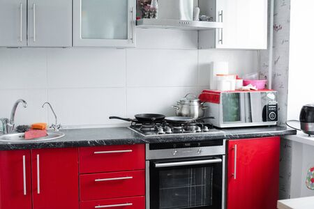 Beautiful modern clean red kitchen in small apartment full shot