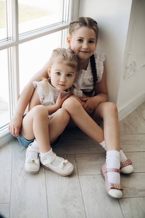 Photo pour Two sisters sitting near window and hugging each other - image libre de droit