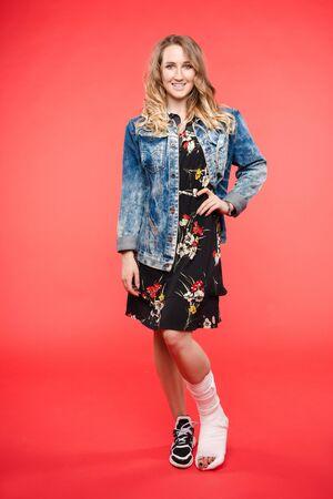 Photo pour Pretty woman in short dress posing with broken leg - image libre de droit