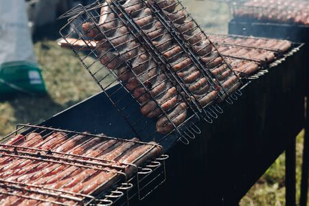 Heap of fresh appetizing sausage cooking on barbecue grill ready for outdoor picnic top view