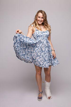 Photo pour Pretty woman in short dress posing with broked leg - image libre de droit