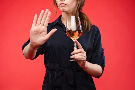 Photo for Woman with a glass of wine gesturing hand with stop sign.Isolate over red background. - Royalty Free Image
