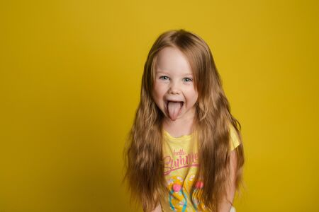 Photo for Portrait of beautiful little girl with long hair smiling posing isolated at yellow studio background - Royalty Free Image