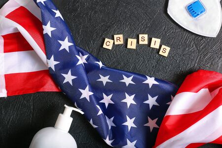Photo pour The crisis in the United States due to the global pandemic. The consequences of the coronovirus. American flag and virus protection on a dark background top view. The problems of the American population against the background of the epidemic - image libre de droit