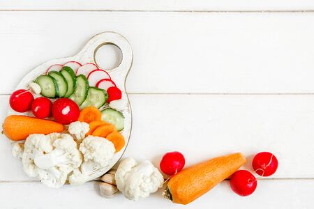 Vegetable slicing on a round white cutting Board. A Board on a white wooden table. There are a few more fresh vegetables nearby. Flat layout with space for text