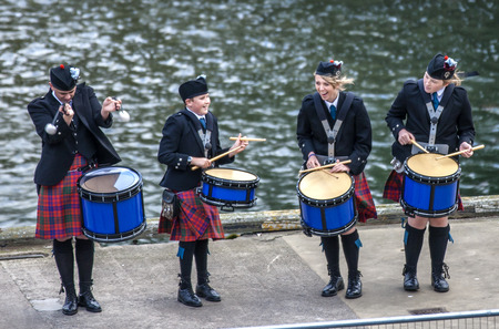 A Scottish band acts as host upon arrival of transatlantic ships in the port of Invergordon in Scotland committee. The orchestra, made up of amateur musicians in the region, seems playful at the many mistakes played by musicians.
