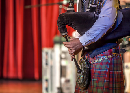 Scottish musicien bagpiper from a Scottish band acts as host upon arrival of transatlantic ships in the port of Invergordon in Scotland committee.