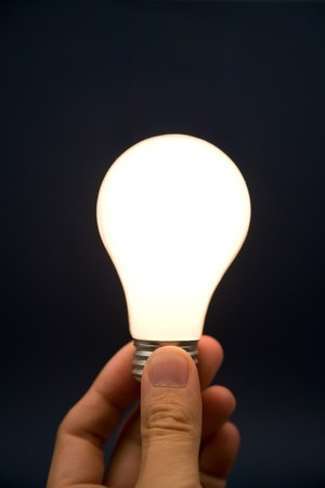 Hand holding a Bright Light Bulb, Concept of Inspiration, Ideas