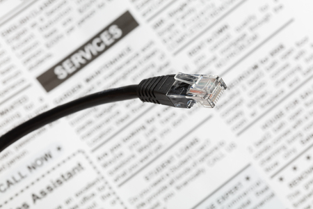 Photo for Black network cable plug with fake newspaper , close up view. - Royalty Free Image