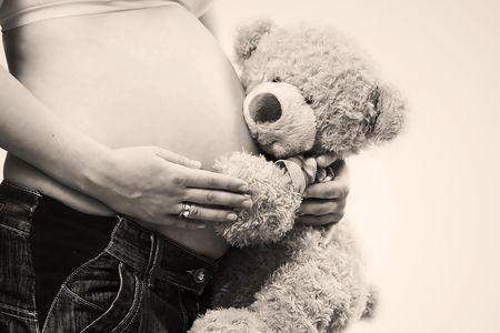 pregnant belly being hugged by cute teddy bear