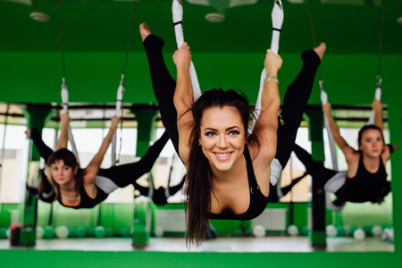 Photo for young women making antigravity yoga exercises with a group of people. aero fly fitness trainer workout. white hammocks. - Royalty Free Image