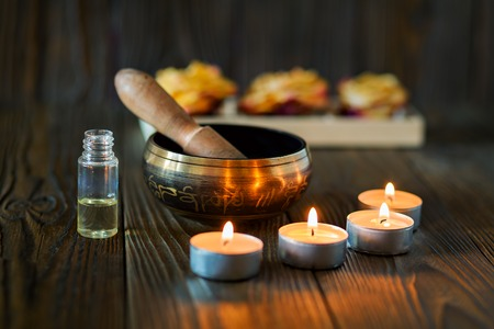 Photo pour Singing bowl on dark wooden background. Burning candles and oil for aromatherapy and massage. - image libre de droit