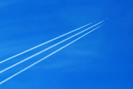 Three military jet planes with contrail in the clear blue sky