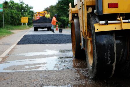Photo for Repairing a damaged road By adjusting the level with asphalt mixed with small stones And then compacted with a vibratory compactor - Royalty Free Image