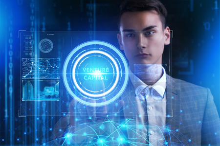 Foto de The concept of business, technology, the Internet and the network. A young entrepreneur working on a virtual screen of the future and sees the inscription: Venture capital - Imagen libre de derechos