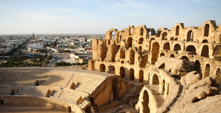 Amphitheatre with El Djem city skyline in Tunisia  Arches and auditorium of roman biggest amphitheater in africa with city skyline of El Djam in the background, Tunisia