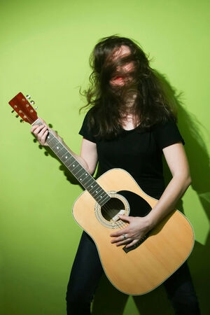 Portrait of a young woman playing the guitar and shaking her hair with green background.