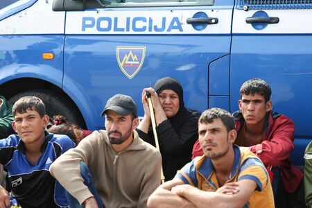Bregana, Slovenia - September 20, 2015 : A group of syrian refugees sitting next to a police vehicle on the slovenian border with Croatia. The migrants are waiting for the authorities to open the border crossing, so they can continue to the northern europ