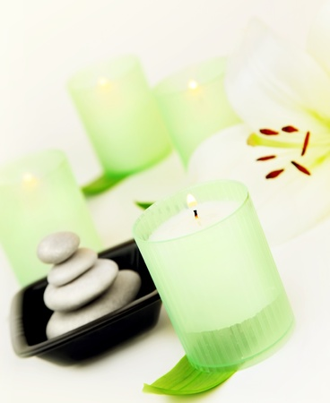 Candles and balanced zen spa stones with lily flower, relaxation vacation concept