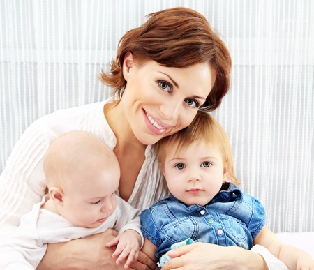Photo pour Happy family at home, loving mother hugging her kids - image libre de droit
