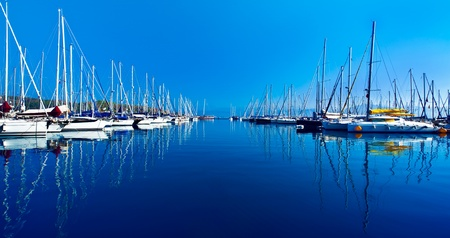 Photo for Yacht port over blue nature scene, row of luxury sailboats reflected in water  - Royalty Free Image